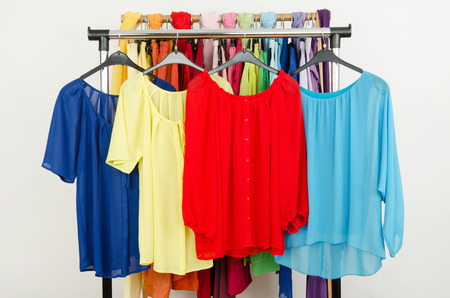 blouses: Cute red, yellow, blue blouses displayed on a rack. Wardrobe with colorful summer clothes and accessories. Stock Photo