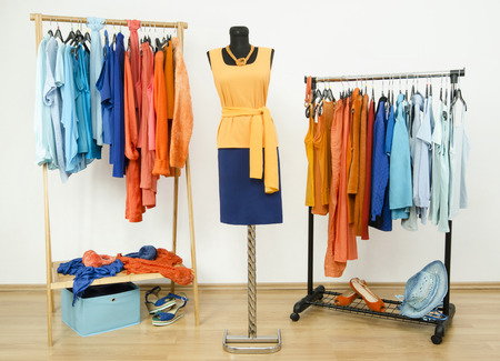 complementary: Wardrobe with complementary colors orange and blue clothes arranged on hangers. Dressing closet with clothes, shoes and accessories and an outfit on a mannequin. Stock Photo