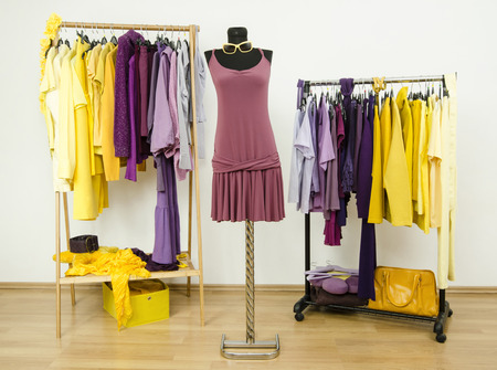 complementary: Dressing closet with complementary colors violet and yellow clothes.Wardrobe with purple and yellow clothes arranged on hangers and a summer dress on a mannequin.