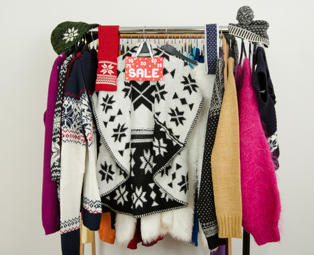 clothes rack: Cute winter sweaters displayed on hangers with a big sale sign. Season clearance rack with colorful winter clothes and accessories.