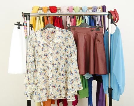 ropa de verano: trajes florales lindo muestran en una rejilla. Armario con ropa de verano de colores y accesorios.