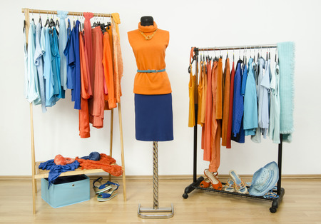 complementary: Wardrobe with complementary colors orange and blue clothes arranged on hangers. Dressing closet with clothes, shoes and accessories and a autumn outfit on a mannequin.