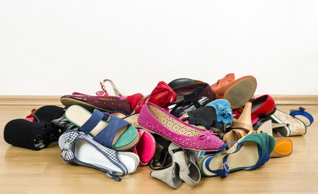 high heel shoes: Close up on big pile of colorful woman shoes. Untidy stack of shoes thrown on the ground.