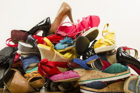 untidy: Close up on big pile of colorful woman shoes. Untidy stack of shoes thrown on the ground.