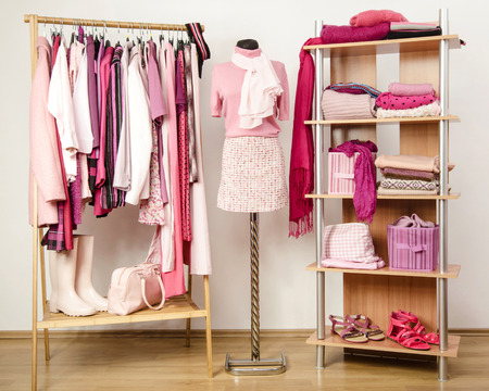 Dressing closet with pink clothes arranged on hangers and shelf, outfit on a mannequin. Wardrobe full of all shades of pink clothes, shoes and accessories. Stockfoto