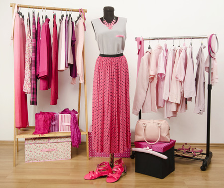 Dressing closet with pink clothes arranged on hangers and an outfit on a mannequin. Wardrobe full of all shades of pink clothes, shoes and accessories. Stock Photo