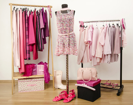 Dressing closet with pink clothes arranged on hangers and an outfit on a mannequin. Wardrobe full of all shades of pink clothes, shoes and accessories. Stockfoto