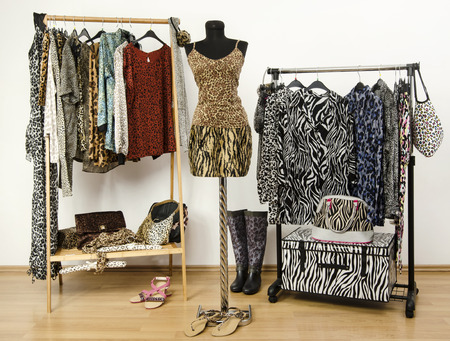 Dressing closet with animal print clothes arranged on hangers. Cheetah print top and tiger print skirt on a mannequin. Colorful wardrobe with jungle pattern clothes and accessories.