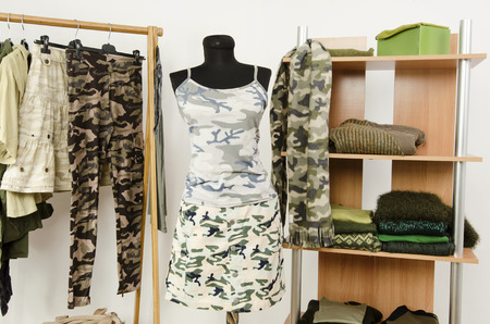 green clothes: Dressing closet with military camouflage khaki green clothes arranged on hangers and shelf, outfit on a mannequin. Wardrobe with camo pattern clothes and accessories. Stock Photo
