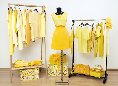 yellow: Dressing closet with yellow clothes arranged on hangers and an outfit on a mannequin. Wardrobe full of all shades of yellow clothes, shoes and accessories.