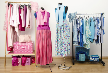 Dressing closet with pink and blue clothes arranged on hangers with outfit on two mannequins. Wardrobe full of all shades of blue and pink clothes, shoes and accessories.