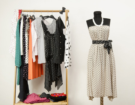 Dressing closet with polka dots clothes arranged on hangers and a dress on a mannequin. Colorful wardrobe with polka dots clothes and accessories.