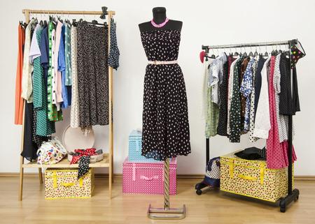 Dressing armadio con pois vestiti disposti su grucce e un vestito su un manichino. guardaroba colorato con pois abiti e accessori. Archivio Fotografico