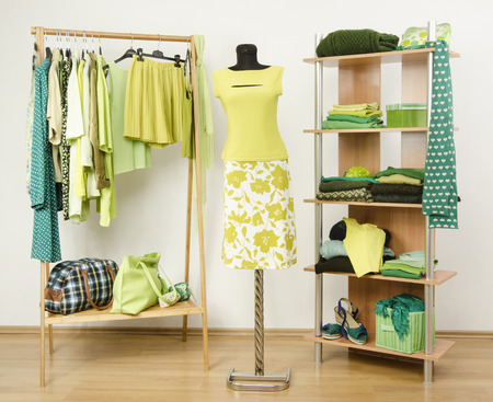 green clothes: Dressing closet with green clothes arranged on hangers and shelf, neon green outfit on a mannequin. Wardrobe full of all shades of green clothes and accessories.