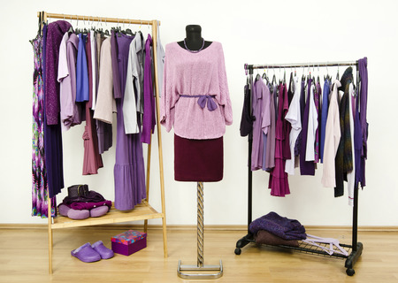 Wardrobe with purple clothes arranged on hangers and an outfit on a mannequin. Dressing closet with all shades of violet clothes, shoes and accessories.