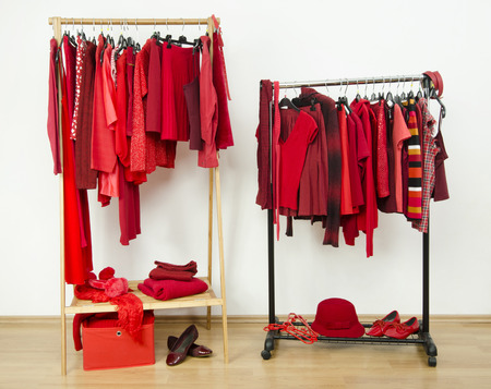 clothes rack: Wardrobe with red clothes hanging on a rack nicely arranged. Red clothes on hangers and accessories in a dressing room.
