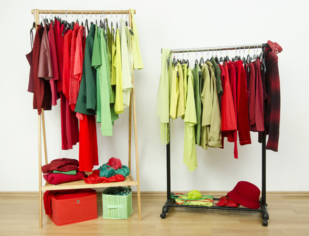 complementary: Dressing closet with complementary colors red and green clothes arranged on hangers. Wardrobe full of all shades of green and red clothes and accessories. Stock Photo