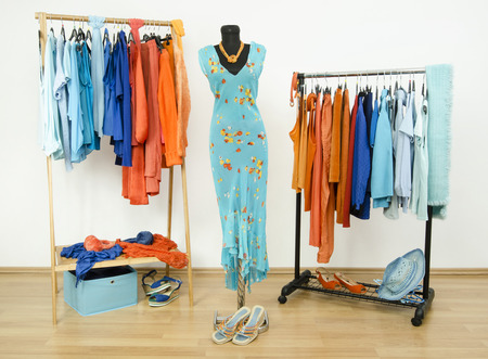 complementary: Wardrobe with complementary colors orange and blue clothes arranged on hangers. Dressing closet with clothes, shoes and accessories and a dress on a mannequin. Stock Photo