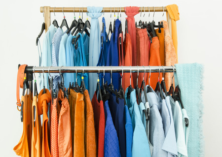 complementary: Close up on complementary colors clothes on hangers in a store. Shades of orange and blue clothes and accessories hanging on a rack nicely arranged.