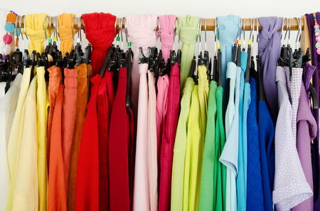 clothes rack: Close up on color coordinated clothes on hangers in a store. All colors clothes hanging on a rack nicely arranged.