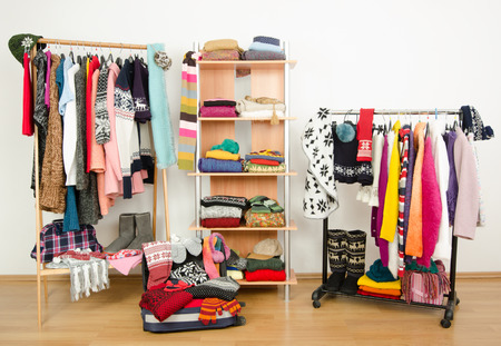 Packing the suitcase for winter vacation. Wardrobe with clothes nicely arranged and a full luggage. Dressing closet with colorful winter clothes and accessories on hangers and a shelf.