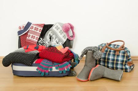 maletas de viaje: Equipaje invierno. Maleta llena de ropa marchita. Embalaje de la maleta para las vacaciones de Navidad. Equipaje completo y una bolsa con ropa y accesorios.