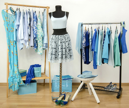 Dressing closet with blue clothes arranged on hangers and an outfit on a mannequin. Wardrobe full of all shades of blue clothes, shoes and accessories.