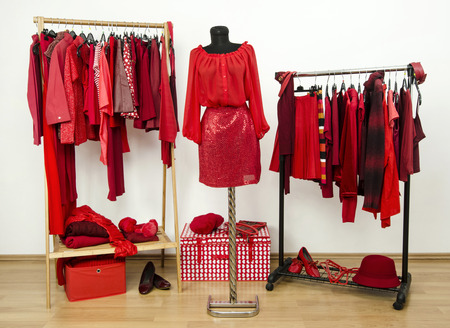 Dressing closet with red clothes arranged on hangers and an outfit on a mannequin. Wardrobe full of all shades of red clothes, shoes and accessories.