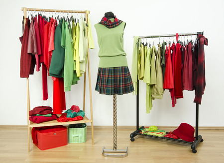 complementary: Dressing closet with complementary colors red and green clothes arranged on hangers and an outfit on a mannequin. Wardrobe full of all shades of green and red clothes and accessories.