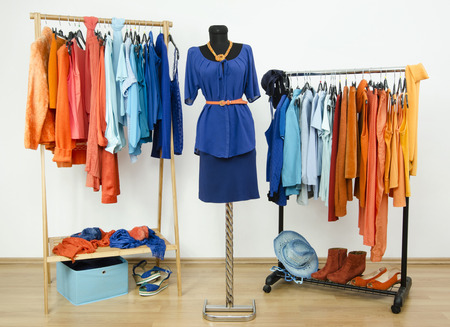 complementary: Dressing closet with complementary colors blue and orange clothes arranged on hangers and an outfit on a mannequin. Wardrobe full of all shades of blue an orange clothes, shoes and accessories. Stock Photo
