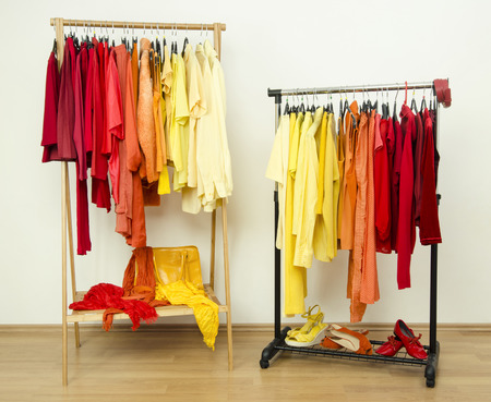 clothes rack: Color coordinated clothes on hangers. Shades of yellow, orange and red clothes hanging on a rack nicely arranged. Stock Photo