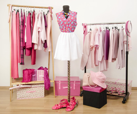 Dressing closet with pink clothes arranged on hangers and an outfit on a mannequin. Wardrobe full of all shades of pink clothes, shoes and accessories. Фото со стока