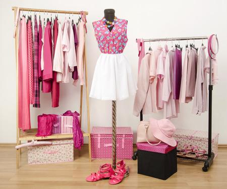 Vestir armario con ropa de color rosa dispuestas sobre perchas y un traje en un maniquí. Armario lleno de todos los tonos de ropa de color rosa, zapatos y accesorios. Foto de archivo - 44217116