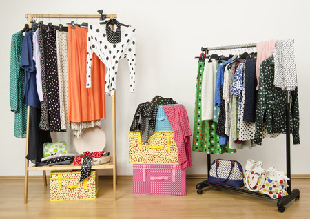 clothes rack: Dressing closet with polka dots clothes arranged on hangers. Colorful wardrobe with polka dots clothes on a rack and accessories.