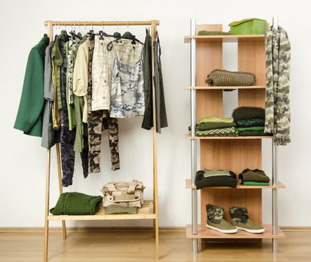 green clothes: Dressing closet with military camouflage khaki green clothes arranged on hangers and shelf. Wardrobe with camo pattern clothes, shoes and accessories.