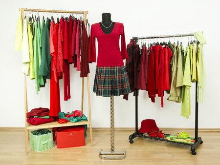 complementary: Dressing closet with complementary colors red and green clothes arranged on hangers and a plaid outfit on a mannequin. Wardrobe full of all shades of green and red clothes and accessories.