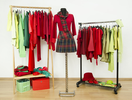 green clothes: Dressing closet with complementary colors red and green clothes arranged on hangers and a plaid outfit on a mannequin. Wardrobe full of all shades of green and red clothes and accessories.