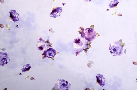 Floral pattern on purple fabric. Mauve rose flower print as background. Standard-Bild