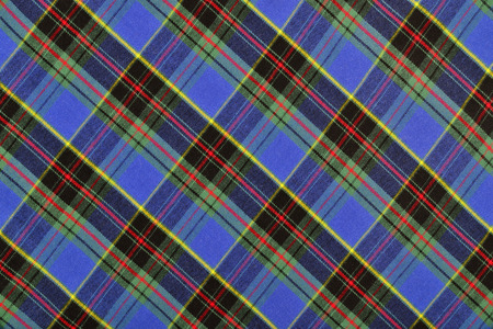 linen fabric: Scottish tartan pattern. Blue with red and yellow plaid print as background. Symmetric rhombus square pattern.