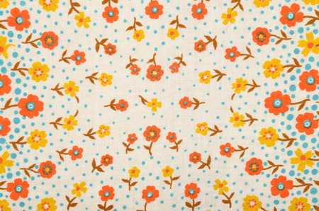 retro fashion: Floral pattern on fabric. Yellow and orange flowers with blue dots print as background.