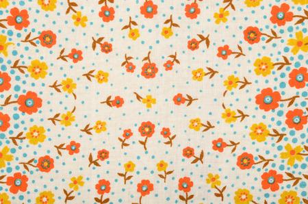 patrones de flores: Modelo floral en tela. flores de color amarillo y naranja con puntos azules se imprimen como fondo.