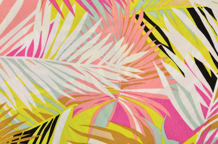 Colorful tropical leaves pattern on fabric. Pink, yellow and white palm leaves print as background. Stockfoto