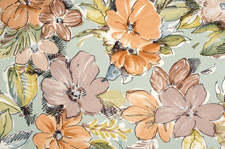 flower patterns: Modelo floral en tela azul. Brown y flores de color naranja se imprimen como fondo. Foto de archivo