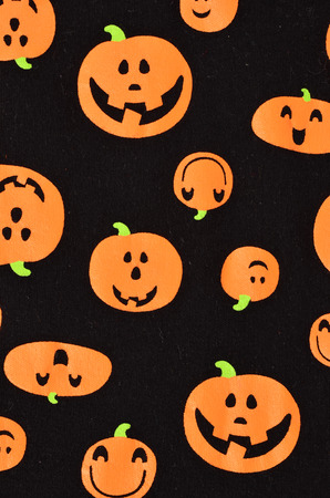fun background: Halloween orange pumpkins on black fabric. Cute scary smiling craved pumpkins pattern as a background.
