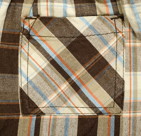 red plaid: Pocket on pants with Scottish tartan pattern. Brown with red and blue plaid print as background.