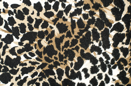 spotted fur: Brown and black leopard fur pattern. Spotted animal print as background. Stock Photo