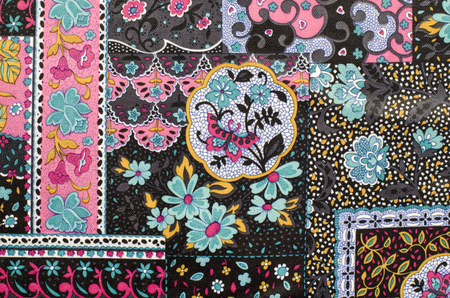 decoration design: Abstract floral pattern on fabric. Colorful flowers and motif print as background.