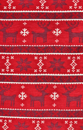 christmas motif: Red textile Christmas pattern as a background. Close up on red material fabric with winter motif, snowflakes and reindeer in a row.