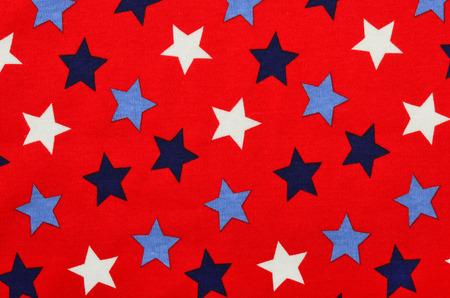 estrellas cinco puntas: Azul estrellas en tela roja de cinco puntas. Estrellas blancas y azules como fondo. Foto de archivo