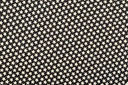 estrellas cinco puntas: Estrellas del blanco en tejido negro de cinco puntas. Muchas estrellas blancas como fondo.